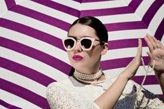 一俏丽的年轻女人的画象白色鞋带礼服、白色珍珠项链和太阳镜的有明亮的被绘的嘴唇的 库存图片
