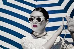一俏丽的年轻女人的画象白色鞋带礼服、白色珍珠项链和浅粉红色的太阳镜的 图库摄影