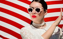 一俏丽的年轻女人的画象白色鞋带dess、白色珍珠项链和太阳镜的有霓虹红色被绘的嘴唇的 免版税库存照片