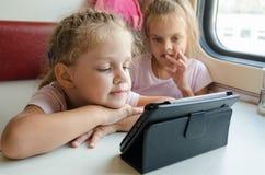 一列火车的两个女孩有看动画片的兴趣的压片个人计算机 免版税库存照片