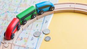 一列玩具火车和一条木铁路在城市和硬币的地图 火车旅行在国家周围 免版税图库摄影