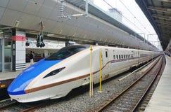 一列蓝色和白色E7系列Shinkansen高速高速火车 免版税库存图片