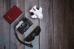 一副护照、葡萄酒照相机、小飞机和太阳镜在木桌上 免版税库存图片