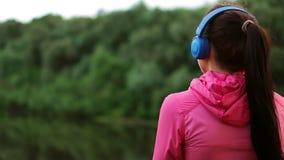 一副桃红色夹克和蓝色耳机的一个女孩站立与她并且清早看河在奔跑以后 股票视频