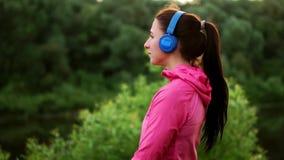 一副桃红色夹克和蓝色耳机的一个女孩站立与她并且清早看河在奔跑以后 影视素材