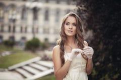 一副白色礼服和白色手套的年轻美丽的女孩 免版税库存图片