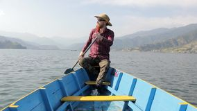 一副红色衬衣、帽子和太阳镜的有胡子的人在荡桨在湖的一条蓝色木小船桨反对山的背景 股票录像