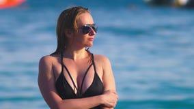 一副黑游泳衣和黑太阳镜的白肤金发的女孩在一白色沙滩 与身体的美好的模型晒日光浴 影视素材