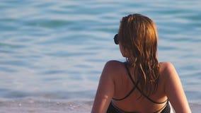 一副黑游泳衣和黑太阳镜的白肤金发的女孩在一白色沙滩 与身体的美好的模型晒日光浴 股票录像