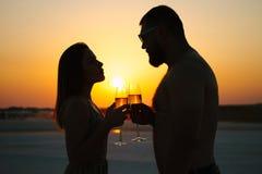 一加上的剪影在日落背景、人和妇女叮当响的酒杯的玻璃用在日落剧烈的sk的香槟 免版税库存照片