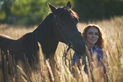 一匹少妇和马的画象在草甸在晴朗的夏天 库存图片