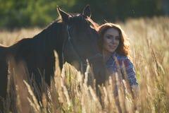 一匹少妇和马的画象在草甸夏天晚上 免版税图库摄影