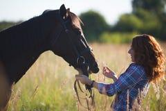 一匹红色头发妇女和马的画象在草甸在晴朗的夏天 免版税库存照片