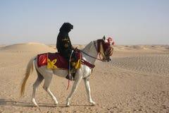 一匹马的人在沙漠 免版税库存图片