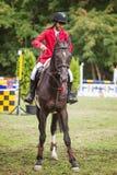 一匹马的女骑士在红色 免版税库存照片