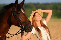 一匹马的妇女在领域 免版税库存照片