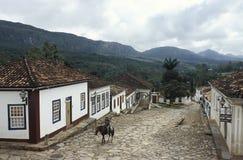 一匹马的老人沿一条未损坏的殖民地街道在Tiraden 免版税库存图片