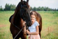 一匹马的逗人喜爱的小女孩在夏天领域礼服 晴朗的日 库存照片
