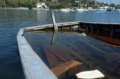 一半下沉的小渔船用水填装了 免版税库存图片