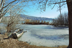 一半下沉的小船在冻湖 库存照片