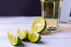 一半与切片的石灰和杯在一张木白色桌上的柠檬水 中央焦点和拷贝空间 库存照片