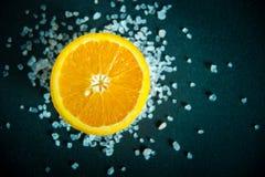一半与喜马拉雅桃红色盐水晶的一个桔子在黑暗的背景 免版税库存照片