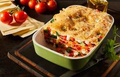 一半健康新鲜蔬菜烤宽面条被吃的盘  免版税库存图片