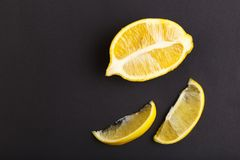 一半和两个切片在黑背景的柠檬是 c新鲜的健康桔子样式维生素 库存图片