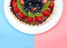 一半在板材桃红色蓝色背景的一个新鲜的夏天果子饼 免版税库存照片