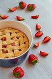 一半在烘烤盘的自创大黄草莓饼在灰色厨房背景 素食饼 库存图片
