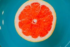 一半在蓝色背景的葡萄柚 库存图片