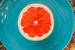 一半在蓝色背景的葡萄柚 免版税库存图片