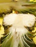 一半在黄色bacground的水多的新鲜的菠萝 图库摄影
