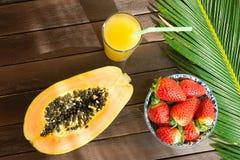 一半成熟在碗菠萝柑橘汁的番木瓜新鲜的草莓在与秸杆棕榈叶的高玻璃在板条木头表上 免版税库存图片