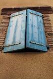 一半打开了在一个棕色大厦门面的木蓝色窗口快门 图库摄影