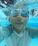 一半淹没了使用在水池的四岁的亚裔男孩 免版税库存照片