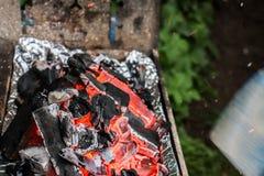 一半烧了与飞行的火花的煤炭  库存照片