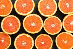 一半背景桔子 水多的桔子切成两半 库存图片