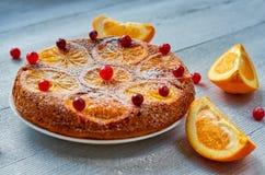 一半自创橙色蛋糕装饰用新鲜的红色蔓越桔和橙色切片在灰色背景 柑橘饼 平的位置 库存图片