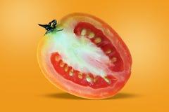 ?? 一半蕃茄,切片蕃茄,在桔子隔绝的飞行蕃茄 库存照片
