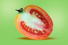 ?? 一半蕃茄,切片蕃茄,在绿色隔绝的飞行蕃茄 库存图片