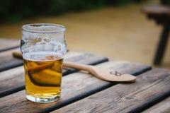一半被喝的品脱与一把木匙子的贮藏啤酒在背景中我 库存图片