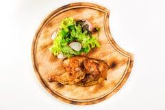 一半被烘烤的鸡用沙拉和萝卜在木回合 免版税库存照片