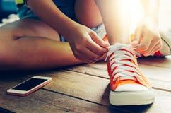 一双少妇鞋带和红色运动鞋的手 免版税库存照片