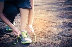 一双少妇鞋带和绿色运动鞋的手 穿上鞋子standi 免版税库存图片