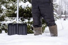 一双感觉的鞋子的一个人有铁锹的在深随风飘飞的雪站立和应该扫清道路到房子在乡下 免版税图库摄影