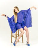 一双清楚的蓝色长袍和蓝色鞋子的美丽的长发金发碧眼的女人 免版税库存照片