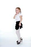 一双白色女衬衫、黑裙子和她的母亲的鞋子的快乐的女孩 免版税库存照片
