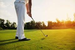 一双白色衣服和黑鞋子的一个人打高尔夫球 库存图片