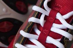 一双红色运动鞋的特写镜头有白色鞋带的 库存图片